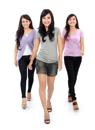 Group of beautiful women walking together isolated over a white background photo