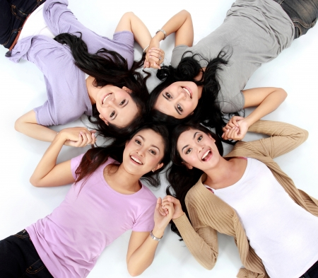 four teenage girls lying on the floor smiling photo