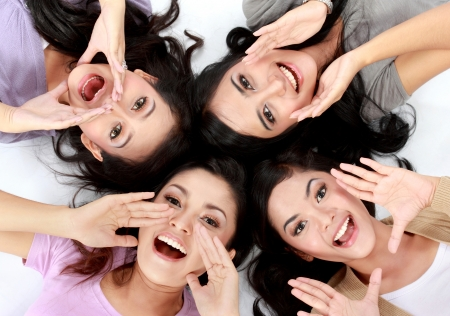 four teenage girls lying on the floor screaming photo