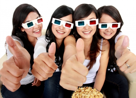 Group of girls watching movie showing thumbs up photo