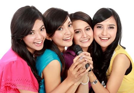 pop singer: Four beautiful young woman singing karaoke together Stock Photo