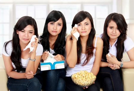 mujer llorando: Grupo de gilrs adolescente sentado en sof� viendo la pel�cula con expresiones tristes Foto de archivo