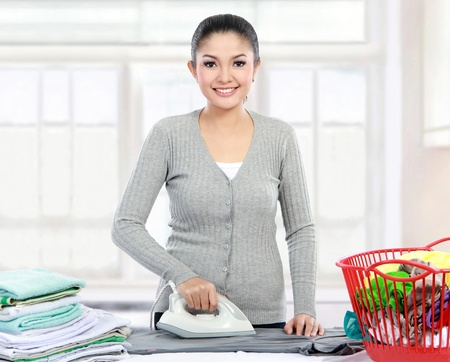 portrait of Happy young beautiful woman ironing clothes