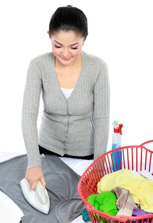 portrait of Happy young beautiful woman ironing clothes photo