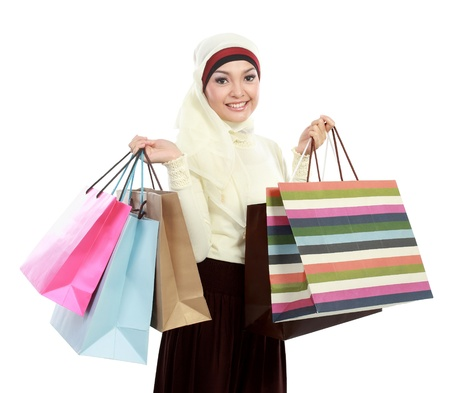 muslimah: Happy young muslim woman with shopping bag isolated over white background