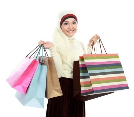 femmes muslim: Heureuse jeune femme musulmane avec sac isol� sur fond blanc
