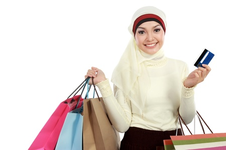 Happy young muslim woman in scarf with shopping bag and credit card photo