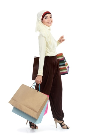 Happy young muslim woman with shopping bag isolated over white background Stock Photo - 18822257