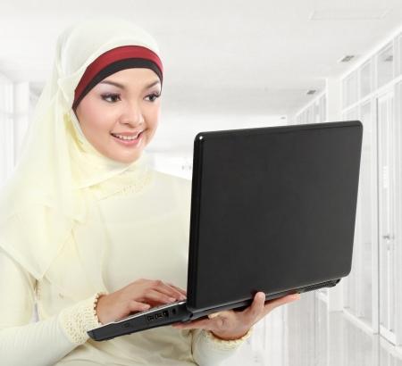 femmes muslim: jeune femme asiatique musulmane en foulard en utilisant un ordinateur portable dans le bureau