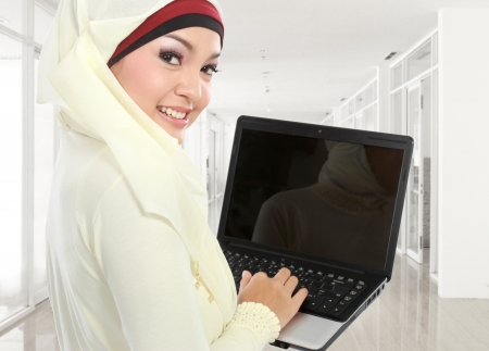young asian muslim woman in head scarf studying using laptop computer in campus photo