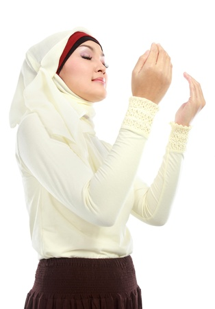 Young beautiful muslim Woman in scarf Praying to god photo