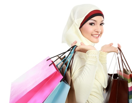 Happy young muslim woman with shopping bag isolated over white background photo