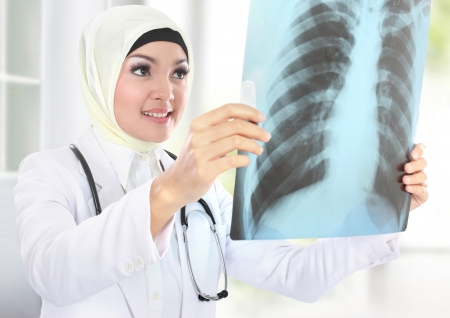 muslim woman: portrait of muslim asian female Medical doctor looking at xray
