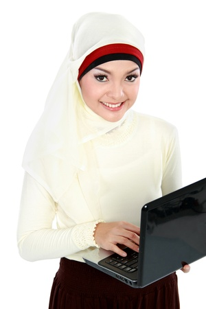 young asian muslim woman in head scarf using laptop computer isolated over white background photo