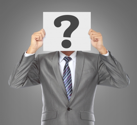 questions: businessman covering his face with big question mark on gray background