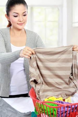 houseclean: beautiful woman doing the laundry at home Stock Photo