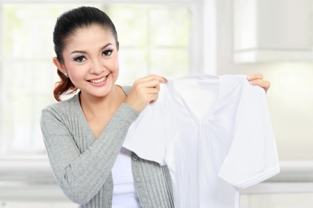 dirty clothes: young smiling asian woman showing white clean clothes Stock Photo