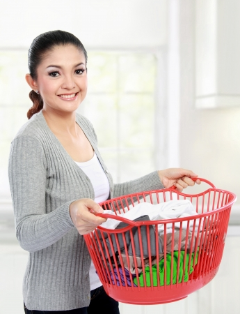 doing laundry: woman doing a housework holding basket of laundry Stock Photo