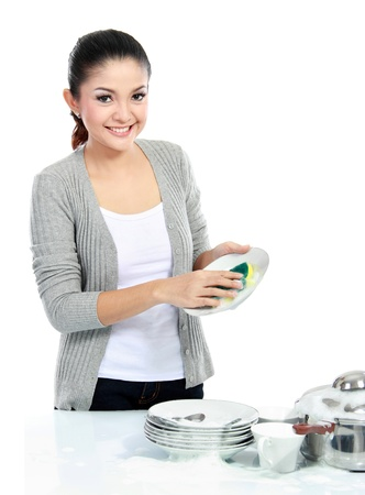 Happy Young Woman Washing Dishes in the kitchen isolated over white background photo
