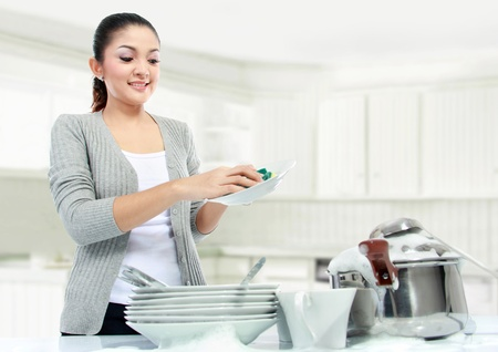 pretty asian woman doing house work, washing dishes photo