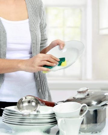 close up of Woman hand Washing Dishes in the kitchen photo