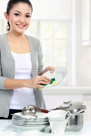 Happy Young asian Woman Washing Dishes in the kitchen photo