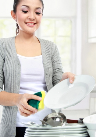 Happy Young Woman Washing Dishes in the kitchen Stock Photo - 18892581