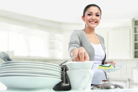 Happy Young Woman Washing Dishes in the kitchen photo