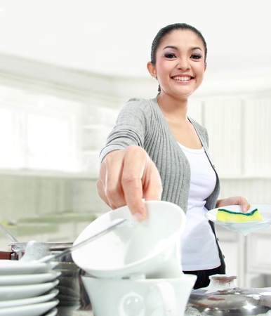 smiling woman happily washing dishes in the kitchen photo