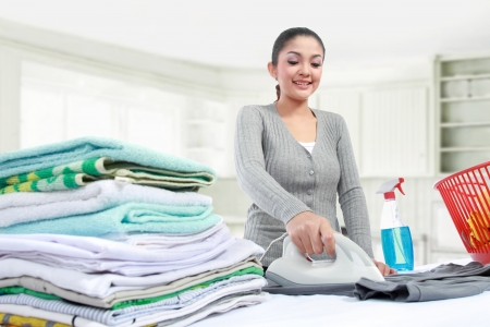 clean  electric: Happy young beautiful woman ironing clothes Stock Photo