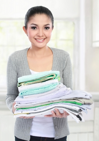 household tasks: smiling woman doing a housework holding stack of clean clothes