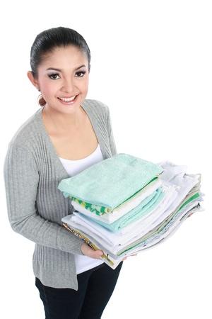 domestic chore: mujer sonriente haciendo una pila de tareas dom�sticas celebraci�n de ropa limpia Foto de archivo