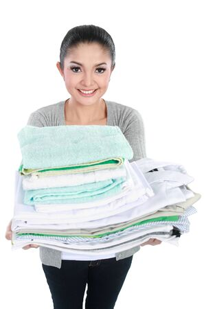 clean clothes: smiling woman doing a housework holding stack of clean clothes