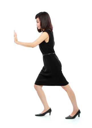 businesswoman in black suit pushing the wall isolated on white background photo