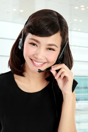 Young beautiful customer service operator with headset in the office Stock Photo - 19093387