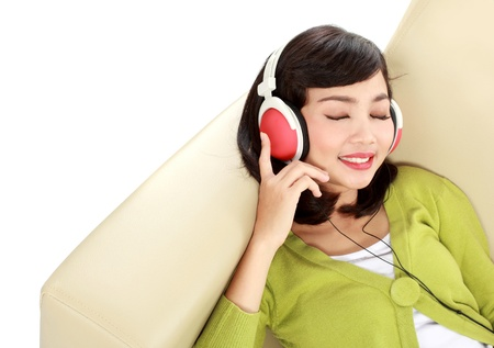 enjoying life: Young attractive woman enjoying music with headphone on the couch Stock Photo