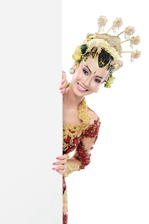 woman wearing traditional dress of java. hiding behind blank white board photo