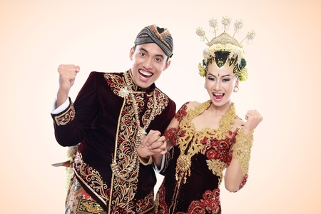 asian bride: happy traditional java wedding couple husband and wife embrace each other