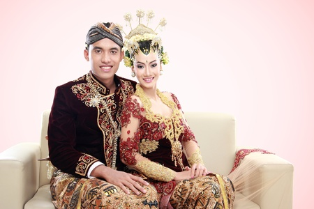 indonesian woman: traditional java wedding couple husband and wife in the couch sitting together