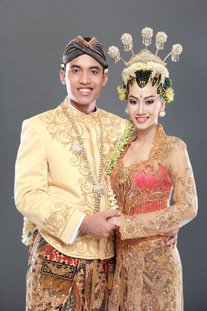 wedding portrait: traditional java wedding couple husband and wife hold each other