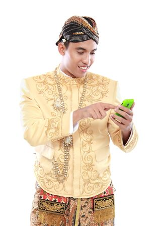 man with traditional java suit using mobile phone isolated over white background photo