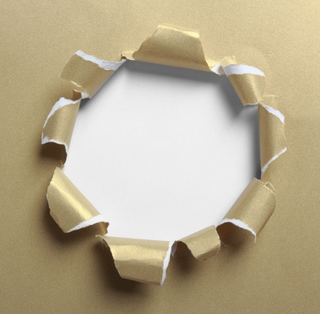 Hole ripped in gold paper on white background photo