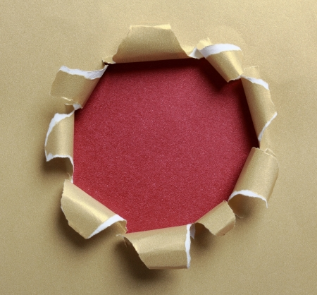 Hole ripped in gold paper on red background photo