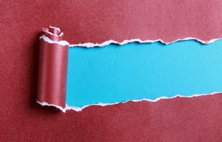 ripped red paper over blue color background photo