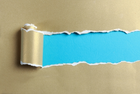 ripped gold paper over blue color background Stock Photo - 20166825