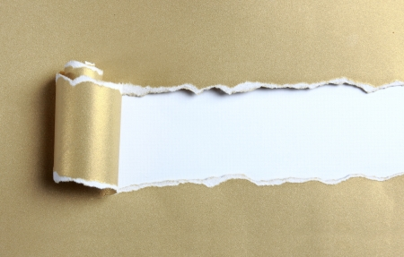 ripped: ripped gold color paper over white background