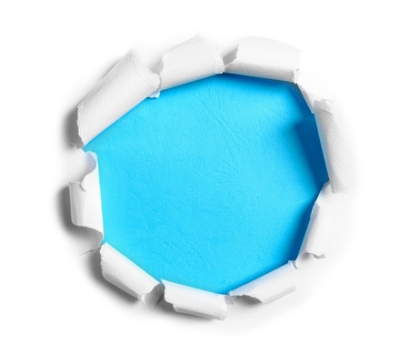 paper scroll: Hole ripped in white paper on blue background Stock Photo