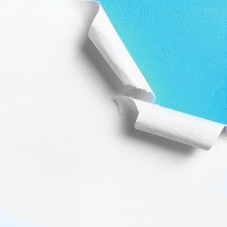 Stuk wit papier met gescheurde gat rand over blauwe achtergrond Stockfoto