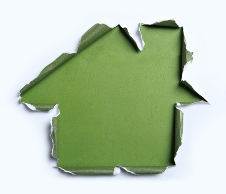 white torn paper with house shape over green background photo