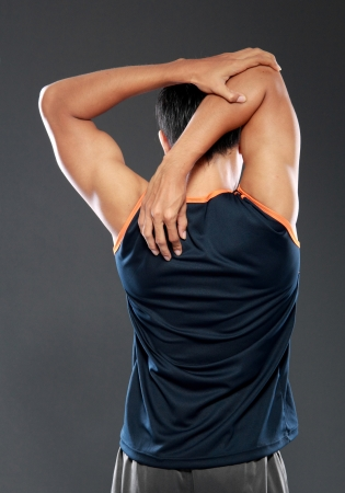 Young male model streching annd looking to the side shot from behind photo